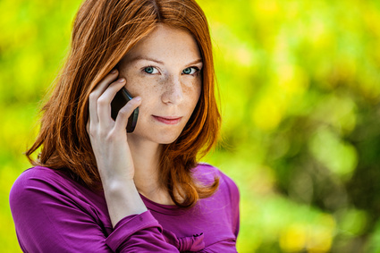 Frau mit Smartphone am Kopf