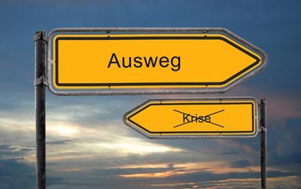 """Zwei Wegweiser mit den Worten """"Krise"""" und """"Ausweg"""""""