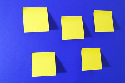 blaue Nachrichtenwand mit gelben Notizzetteln