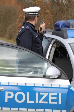 Polizist mit Funkgerät am Fahrzeug