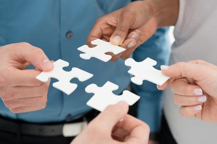 Personengruppe, die Puzzleteile zusammensetzt