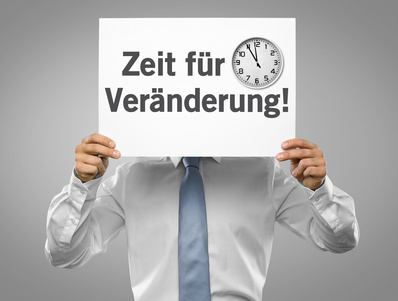 """Ein Geschäftsmann hält ein Plakat """"Zeit für Veränderung"""" vor seinem Kopf"""