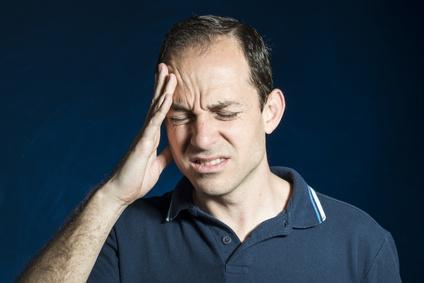 jüngerer Mann mit Kopfschmerzen